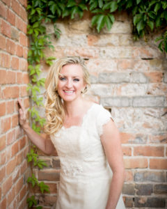 Picture of a bride in her wedding dress with a brick wall in the background