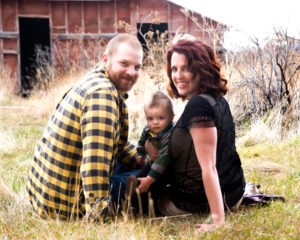 MOSS IMAGE, picture of a mom and dad holding their son while looking back at the camera with a barn in the background