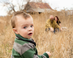 Portrait, Moss Image, MOab Photographer, picture of a boy looking back at the camera with his mom and dad sitting in the background surrounded by yellow grass