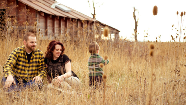 Moss Image, Portrait, Moab Photographer, picture of a mom and dad sitting in front of a barn watching their son play