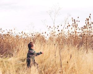 boy in a striped green jacket running through tall grass