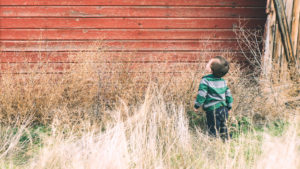 Picture of a boy staring at a red barn
