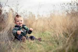 Portrait, Chris Moss, Moab Photographer, picture of a boy sitting in the grass and smiling while looking at the camera