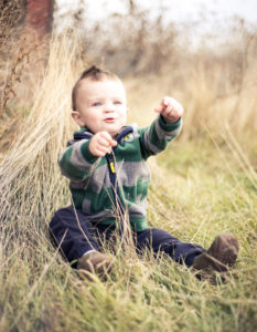 picture of a boy wearing a striped green jacket sitting in the grass and looking up at the sky while pointing at something