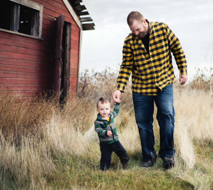 Portrait, Moss Image, Moab Photographer, Dad in a plaid yellow shirt holding a little boys hand wearing a striped green jacked with a barn in the background.
