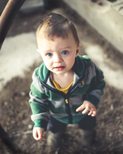 picture of a toddler in a striped green jacket looking up at the camera.