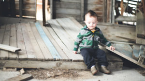 picture of a toddler in a striped green jacket standing in front of a barn.