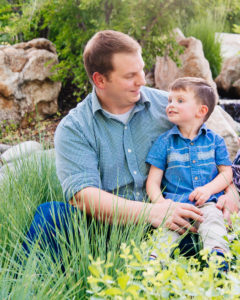 Moss Image, Hansen Family, Moab Photographer, Chris Moss - Dad holding son in grass setting