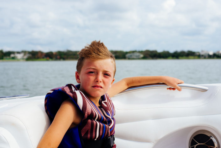 boy on boat in life jacket, moss image, cuba, florida, chris moss