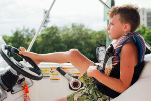 Kid driving boat with feet, moss image, moab photographer, cuba, florida