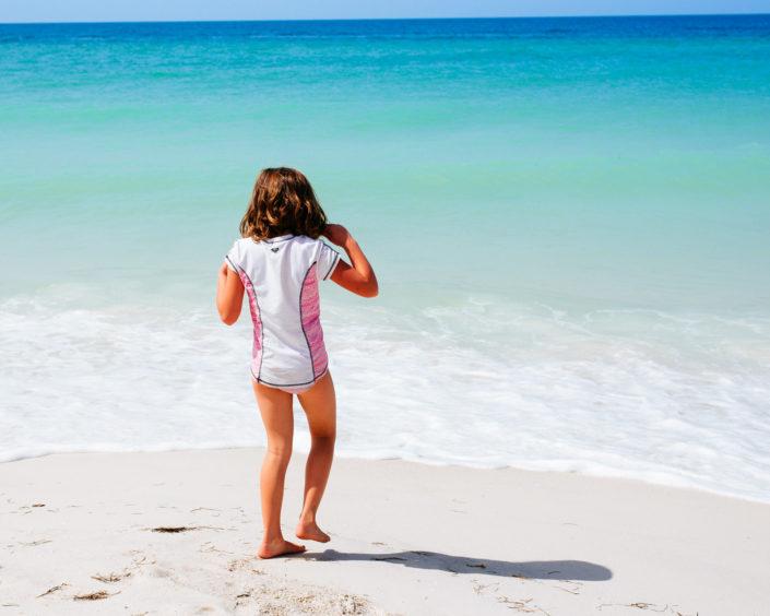 Girl on beach blue water white sand, moss image, moab photographer, chris moss